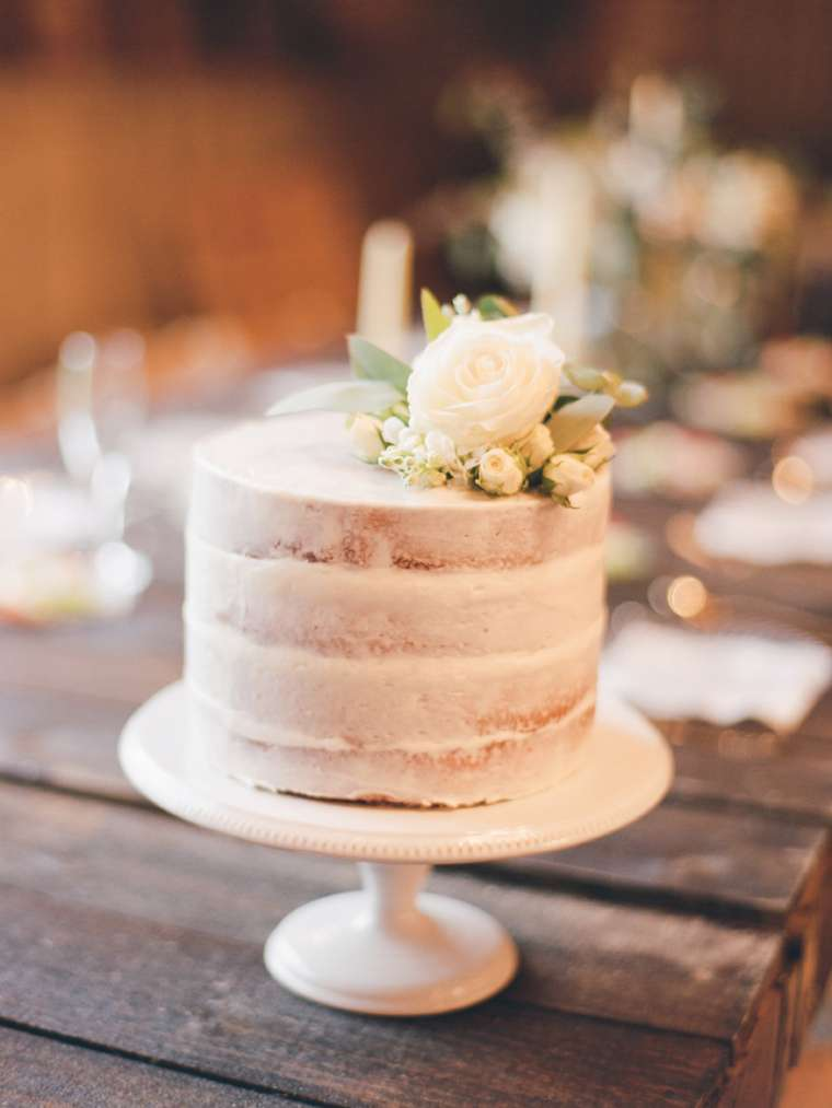Layered naked cake on ivory cake stand with ivory ranuculus on top