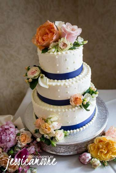 Three-tier ivory wedding cake with navy ribbon and bright florals
