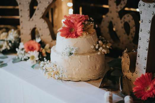 Rustic ivory two-tier wedding cake with flowers