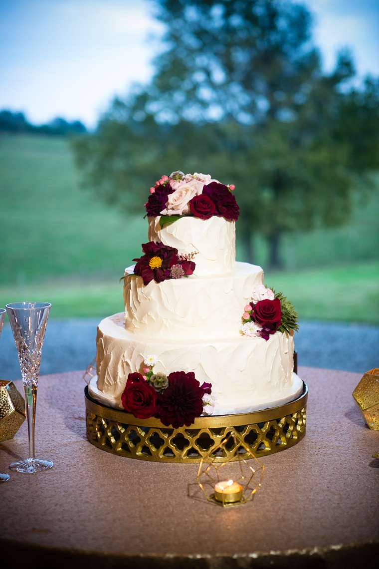 Three-tier ivory textured wedding cake with burgundy flowers on gold cake stand