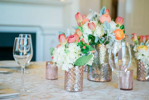 Tulip, ranuculus and hydrangea centerpieces with rose gold vases by Stems, LLC