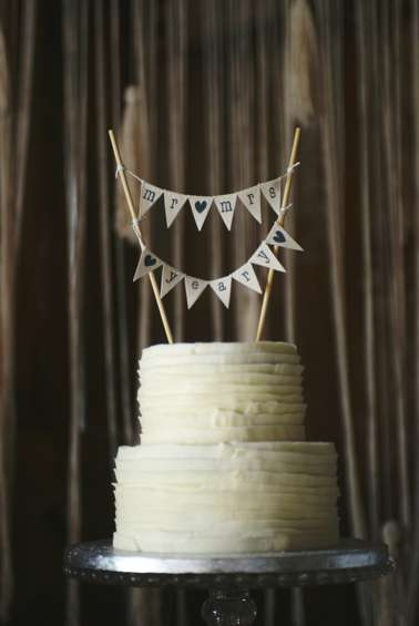 Two-tiered textured ivory wedding cake with pennant banner cake topper