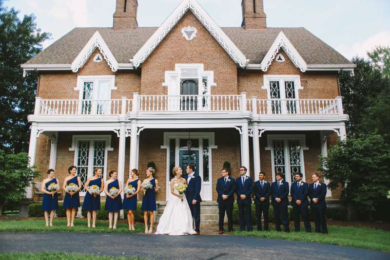 Wedding party dressed in navy in front of home built in 1856