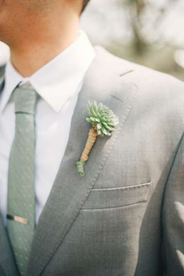 Groom in gray suite with green-gray tie and succulent boutonniere