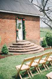 Historic brick cottage with floral swag and moss letter as ceremony backdrop