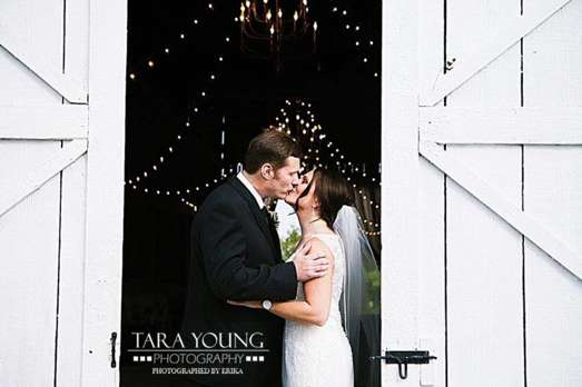 Bride and Groom in front on white barn doors and string lights