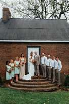Wedding party on the steps of historic cottage