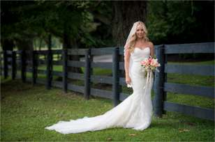 Southern glam bride in field with black fencing