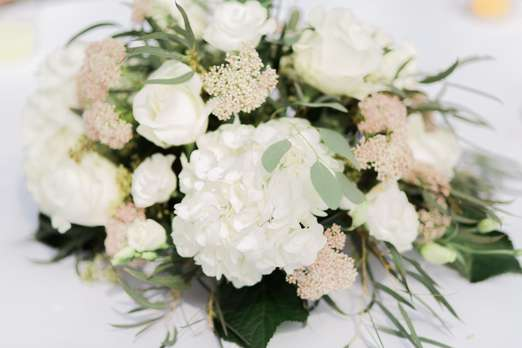 White and soft pink floral centerpiece with eucalyptus. Kaylie Plummer Photography.