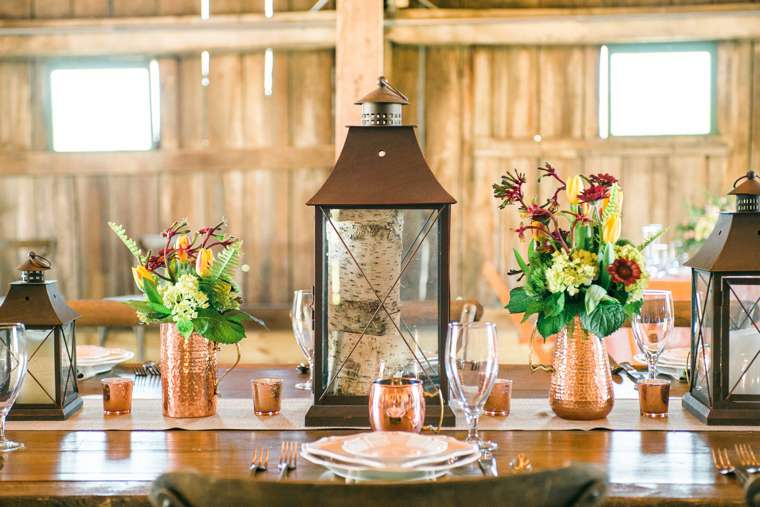 Refined rustic tablescape with lanterns and copper vessels. Bryant's Rent-All, Stems LLC and Keith & Melissa Photography.
