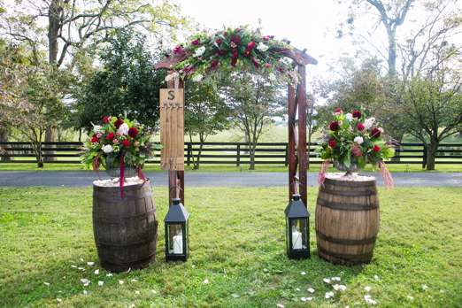 Ceremony backdrop with burgundy floral arch and bourbon barrels