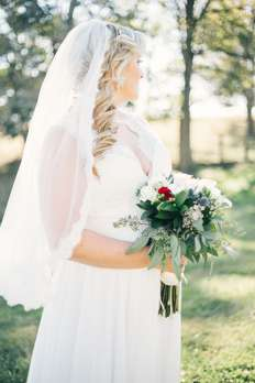 Bride with red, white and blue bridal bouquet and lace lined veil