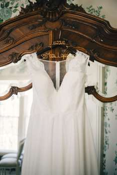 V-neck wedding dress hanging on antique furniture at wedding in historic house