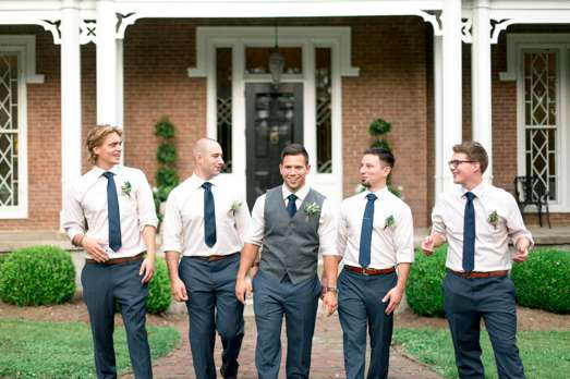 Groom and groomsmen in front of historic manor during KY summer wedding