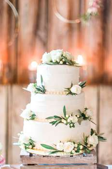 Three-tiered ivory wedding cake with ivory flowers