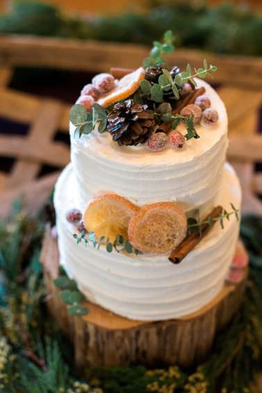 Two-tier winter inspired wedding cake with dried fruit, cinnamon and greenery