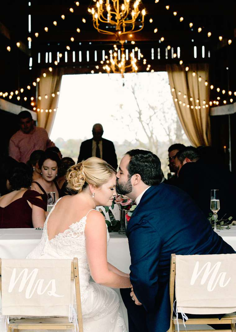 Couple at refined rustic fall barn wedding reception