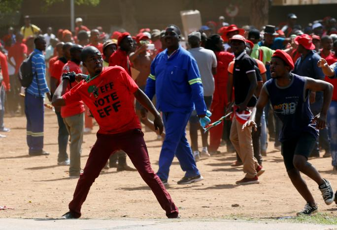 A protester throws a bottle at police during demonstrations calling for the removal of President Jacob Zuma outside the Union Buildings in Pretoria, South Africa, November 2, 2016.  REUTERS/Mike Hutchings