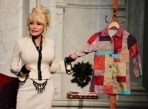 Parton with a replica of the coat that inspired her hit song and book. Both are based on a true story from Parton's childhood: her mother made her a coat out of rags given to the family and taught her to be proud of herself despite growing up in poverty. The book is widely used to discuss and address bullying.