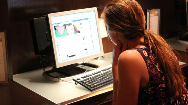 A woman checks her Facebook page at her apartment's computer room in Washington, DC. (UPI/Billie Jean Shaw)
