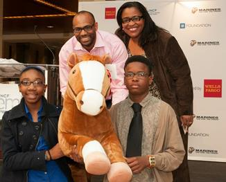 """Wells Fargo leaders Dewey Norwood and Georgette """"Gigi"""" Dixon photographed with two Charlotte students who received Mack, Wells Fargo's commemorative 16oth anniversary pony during the UNCF Empower Me Tour."""