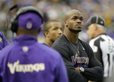 In this Dec. 29, 2013, file photo, Minnesota Vikings running back Adrian Peterson stands on the sidelines during the first half of an NFL football game against the Detroit Lions in Minneapolis.  After a day of public pressure from angry fans and concerned sponsors, the Vikings have reversed course and placed star  Peterson on the exempt-commissioner's permission list, the team announced Wednesday, Sept. 17, 2014. The move that will require him to stay away from the team while he addresses child abuse charges in Texas. (AP Photo/Ann Heisenfelt, File)