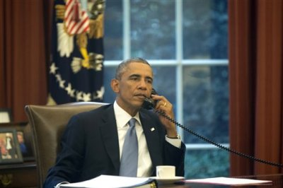 In this image made through a window of the Oval Office, President Barack Obama speaks on the phone to Saudi Arabia's King Abdullah from his desk at the White House in Washington, Wednesday, Sept. 10, 2014, ahead of his address to the nation tonight regarding Iraq and Islamic State group militants. (AP Photo/Charles Dharapak)