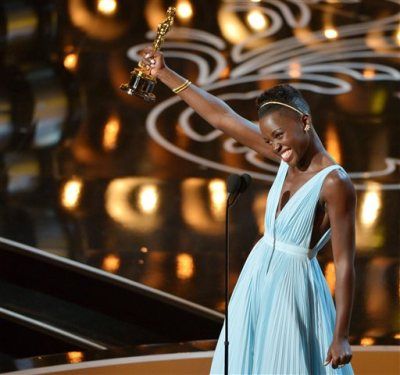 "In this March 2, 2014 file photo, Lupita Nyong'o accepts the award for best actress in a supporting role for ""12 Years a Slave"" during the Oscars in Los Angeles. Nyong'o dazzled Hollywood and the Oscar-viewing public through awards season last year. The Mexican-born, Kenyan-raised actress was a central part last year to an Academy Awards flush with faces uncommon to the Oscar podium. There was Ellen DeGeneres, a proud lesbian, hosting. There was the first Latino, Alfonso Cuaron, winning best director. There was the black filmmaker Steve McQueen hopping for joy after his ""12 Years a Slave"" won best picture. (Photo by John Shearer/Invision/AP, File)"