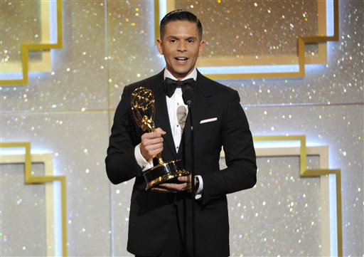 """In this June 22, 2014 file photo, Rodner Figueroa accepts the award for outstanding daytime talent in Spanish for """"El Gordo y la Flaca"""" at the 41st annual Daytime Emmy Awards in Beverly Hills, Calif. Figueroa was fired from Univision after saying that Michelle Obama looks like someone from the cast of """"Planet of the Apes."""" Figueroa, who's known for his biting fashion commentary, made his remarks during a live segment of the show """"El Gordo y la Flaca"""" in which the hosts were commenting on a viral video that shows  a makeup artist transforming  himself into different celebrities, including Michelle Obama. (Photo by Chris Pizzello/Invision/AP, File)"""