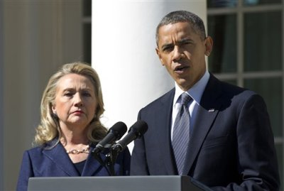 In this Sept. 12, 2012 file photo, President Barack Obama, accompanied by then-Secretary of State Hillary Rodham Clinton, speaks in the Rose Garden of the White House in Washington. Rather than keeping him at arm's length, Hillary Rodham Clinton is embracing President Barack Obama _ sometimes even literally. As she prepares for another presidential campaign, Clinton has aligned herself with Obama far more than she has disagreed with him. She had been expected to separate herself from the president to avoid appearing as though she'd simply carry out his third term.  (AP Photo/Manuel Balce Ceneta, File)