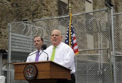 Maryland Gov. Larry Hogan speaks in front of Maryland Secretary of Public Safety and Correctional Services Stephen Moyer at Baltimore City Detention Center, Thursday, July 30, 2015, in Baltimore, to announce his plan to immediately shut down the jail. The jail grabbed headlines in 2013 after a sweeping federal indictment exposed a sophisticated drug- and cellphone-smuggling ring involving dozens of gang members and correctional officers. (AP Photo/Patrick Semansky)