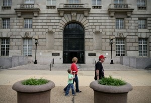 People walk past the EPA building on May 24, the first day of furloughs for the agency. (Mark Wilson/Getty).