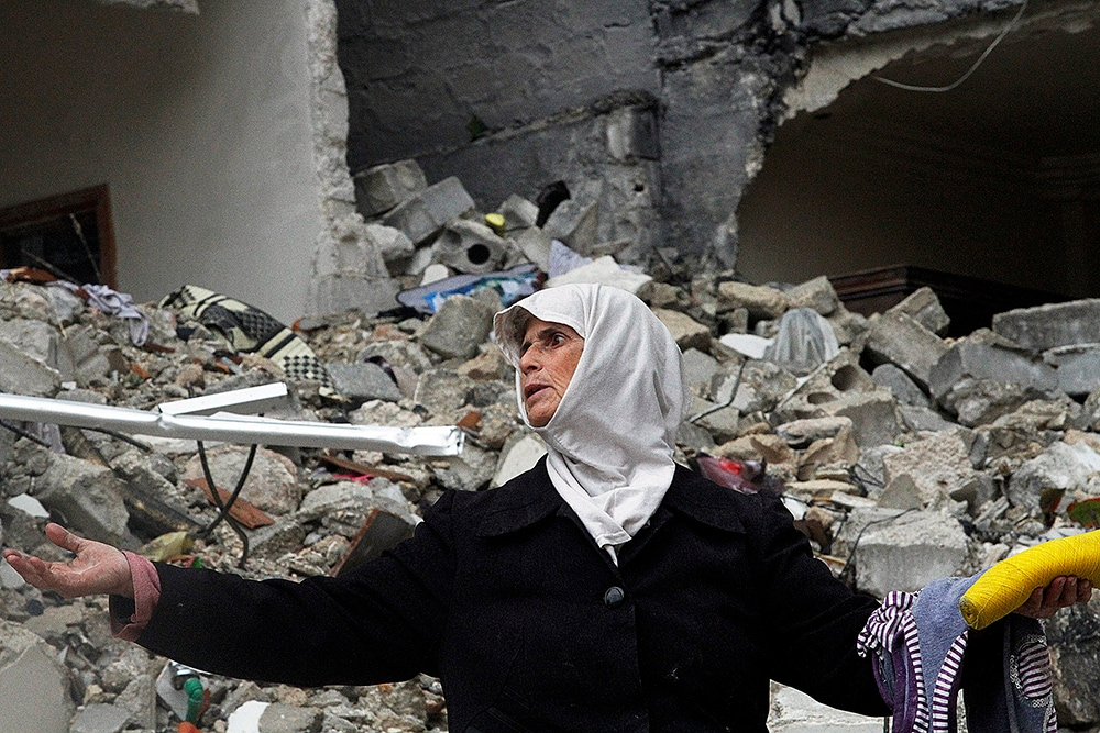 A Syrian woman stands amid the ruins of her house, which was destroyed in an airstrike by government warplanes a few days earlier. (AP Photo/Abdullah al-Yassin, File)