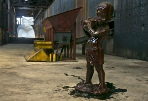 "One of several small sculptures of young boys, covered in molasses, with fruit baskets holding unrefined sugar accompany """"A Subtlety"""" by Kara Walker. (AP Photo/Richard Drew)"