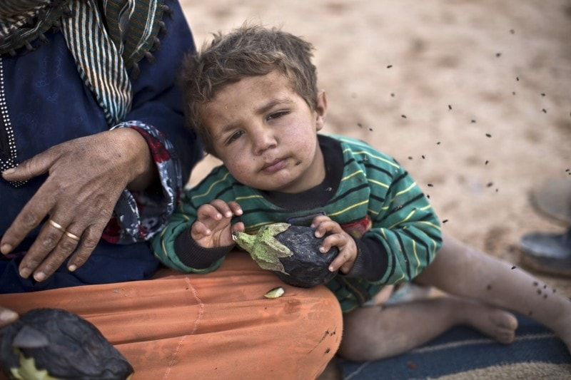 A Syrian refugee child at an informal tent settlement near the Syrian border in Jordan in June. (Muhammed Muheisen/Associated Press)