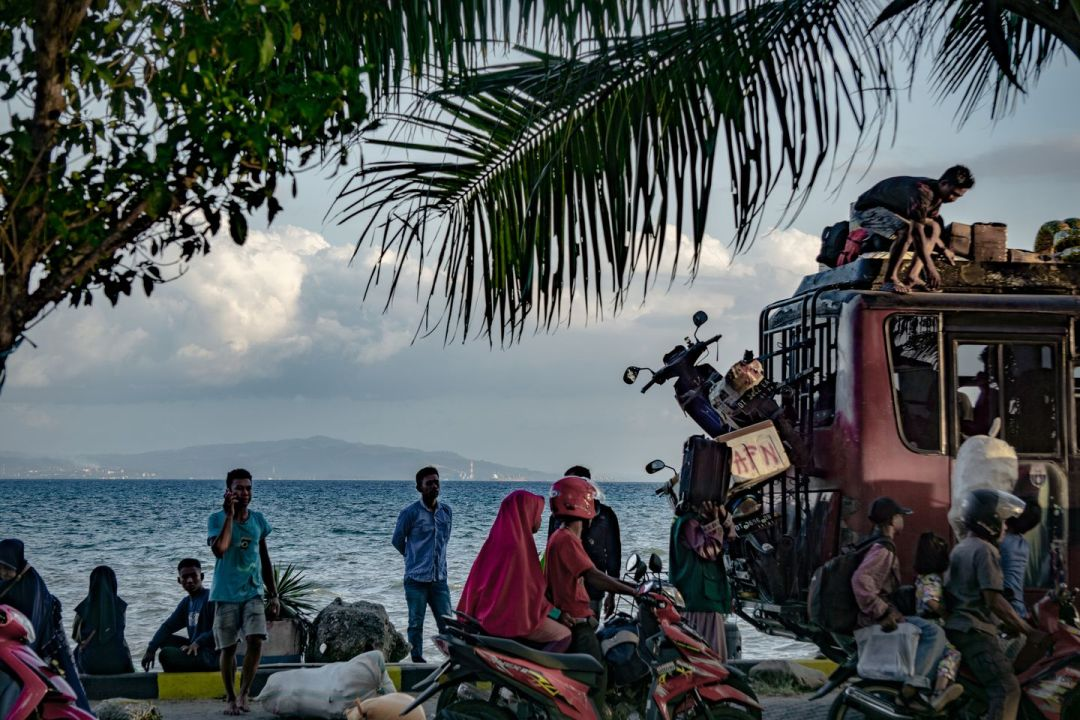 People line up for a ferry in Kolaka, a city that has grown after the emergence of nickel mines and smelters in Pomalaa, seen on the horizon. (Ian Morse for The Washington Post)