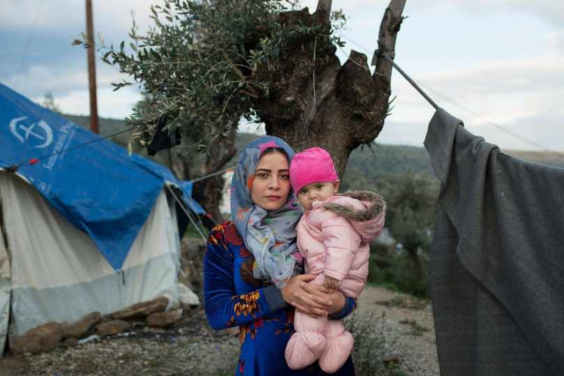 Aya, 21, from Syria, holds her 7-month-old baby at a makeshift camp. (Myrto Papadopoulos for The Post)