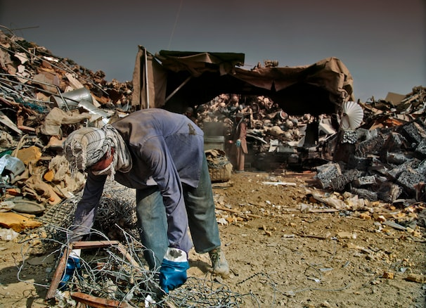 A man collects items from a scrap yard. The U.S. policy has produced more scrap metal than Afghanistan has ever seen. It has also led to frustration among Afghans, who feel as if they're being robbed of items like flat-panel televisions and armored vehicles that they could use or sell — no small thing in a country where the average annual income hovers at just over $500.