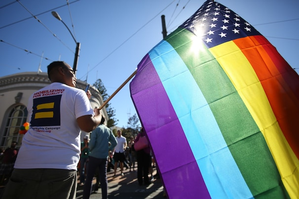 Larry Pascua carries a rainbow flag at a celebration for the U. S. Supreme Court's rulings on Prop. 8 and the Defense of Marriage Act in the Castro District in San Francisco, on Wednesday, June 26, 2013.  In a major victory for gay rights, the Supreme Court on Wednesday struck down a provision of a federal law denying federal benefits to married gay couples and cleared the way for the resumption of same-sex marriage in California. (AP Photo/Mathew Sumner)