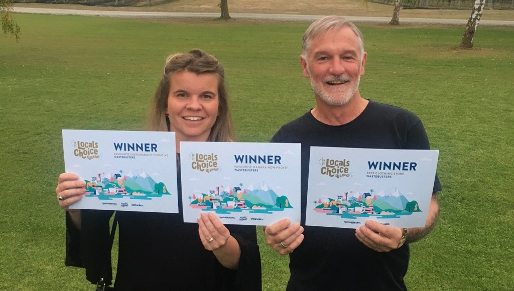 Smiling man and woman hold up three awards certificates which say: winner Wastebusters - Best clothing shop, Favourite sustainability initiative, Favourite Wānaka nonprofit