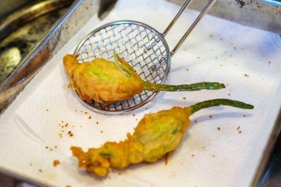 Gefrituurde courgettebloemen, gevuld met mozzarella, ansjovis en basilicum
