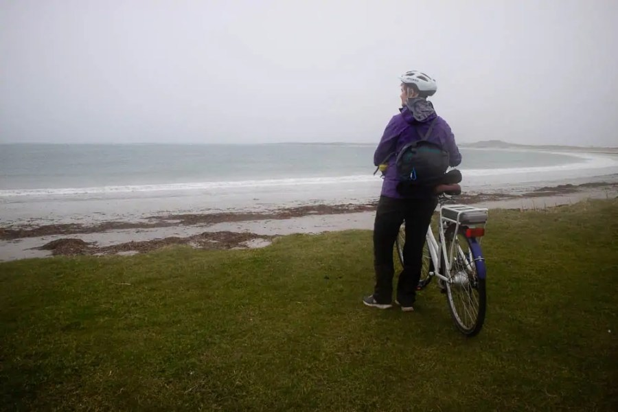 A woman standing by a beach with a bicycle.