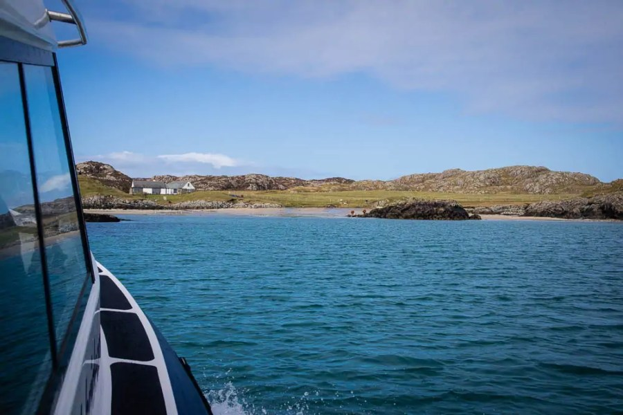 A beach and houses seen from the Isle GO boat on Coll.