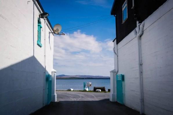 Sea view through the gates of Bruichladdich Distillery on Islay