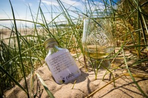 A glass and small bottle of Kilchoman whisky in the sand on a beach.