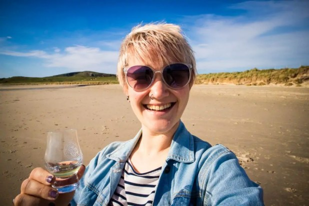 A woman holding a glass of whisky on the beach.