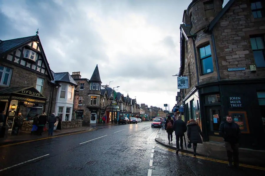 The busy main street of Pitlochry with many shops and pedestrians.