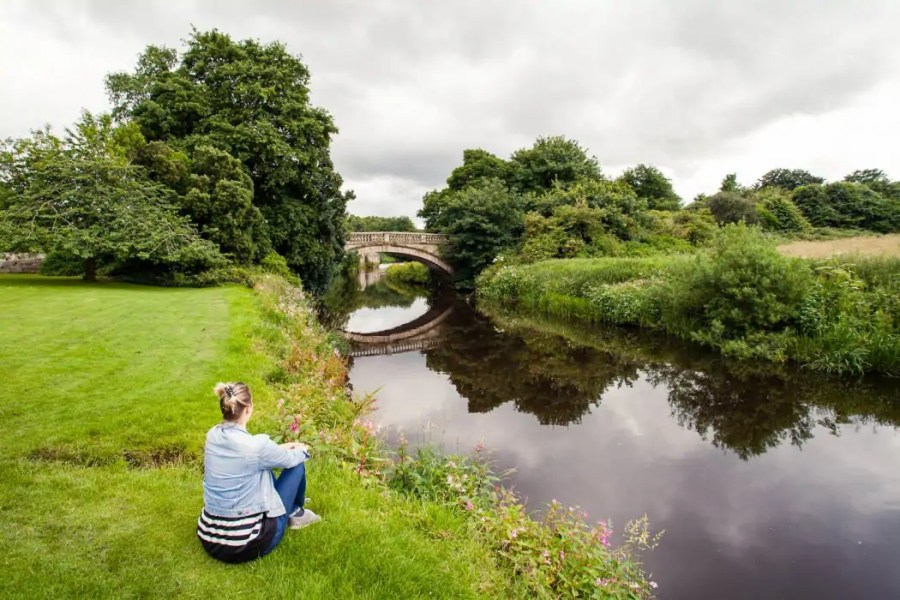 Author Kathi Kamleitner sitting by the water overlooking the old stone bridge at Pollok Country Park in Glasgow.