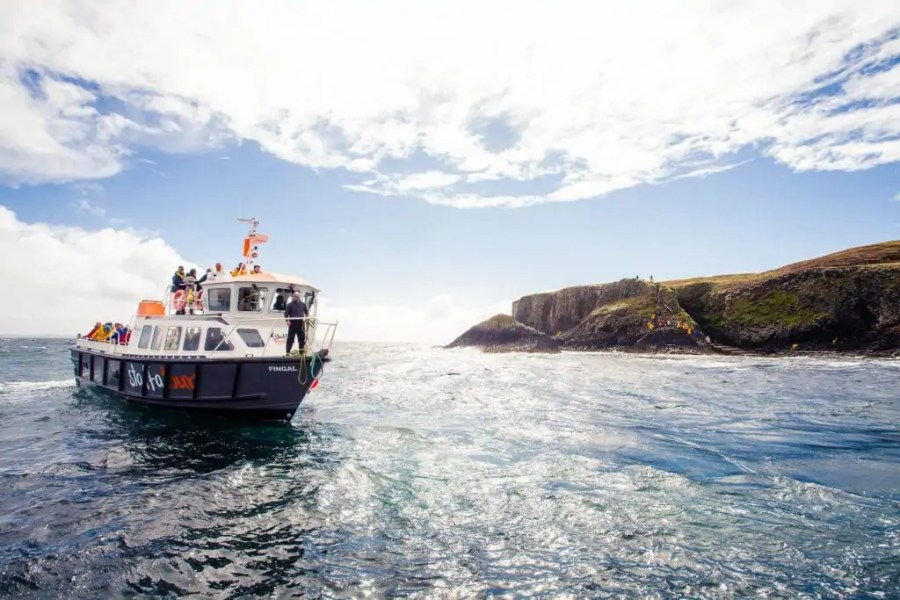A boat from Staffa Tours off the shore of the Isle of Staffa.