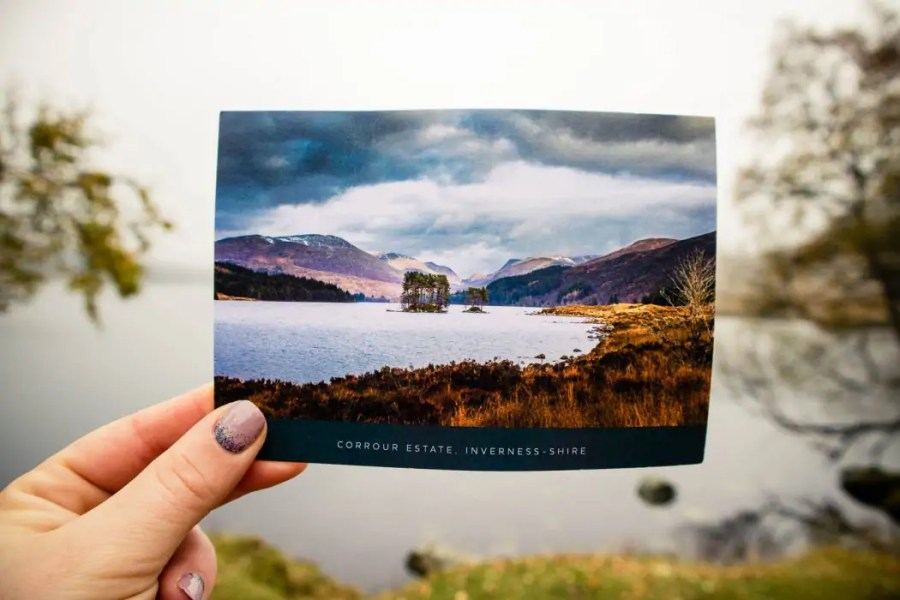 hand holding a postcard of loch ossian near Loch Ossian Youth Hostel